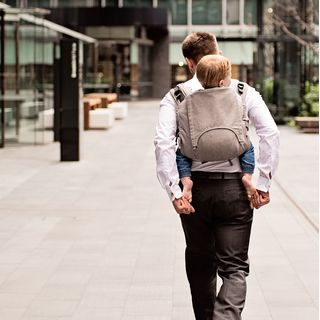 A babywearing dad is wearing his son in a Fidella Chevron -plain umber- Onbuhimo back carrier