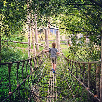 Flo's older son crosses a hanging bridge