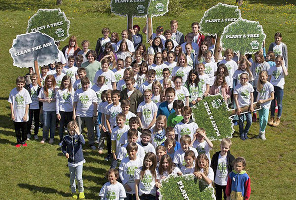 Many children with Plant-for-the-Planet T-shirts stand together.